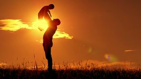 Silhouette of father and son at sunset. The father holds his son`s boy`s hands and kisses him in slow motion. The