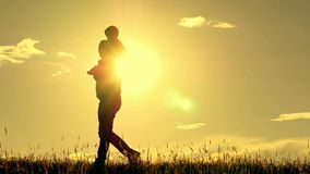 Silhouette of father and son walking on sunset background. Dad is holding his son on his shoulders. The concept of a