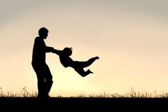 Silhouette of Father Spinning CHild Around Outside royalty free stock image