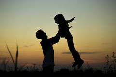 Silhouette of father throwing up his happy daughter in the air at sunset. stock photography