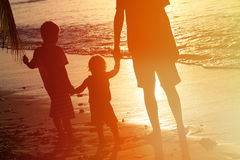 Silhouette of father and two kids walking at sunset stock photo