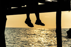 Silhouette of feet of couple sitting on the pier at sunset beach Royalty Free Stock Photos