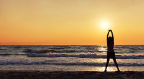 Silhouette of female athlete doing stretches on the beach Royalty Free Stock Photography