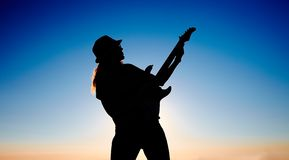 Silhouette of female busker in front of sunrise. Bending body of female musician keeping the guitar on the rising sun background Stock Photos