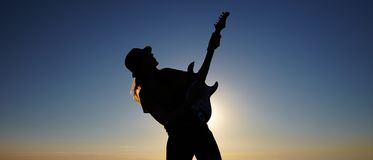 Silhouette of female busker in front of sunrise. Bending body of female musician keeping the guitar on the rising sun background Stock Photography