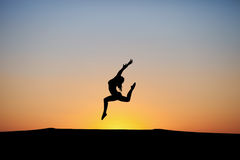 Silhouette of female dancer in sunset sky Royalty Free Stock Photography