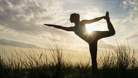 Silhouette female doing a one legged yoga pose at sunset Royalty Free Stock Photos