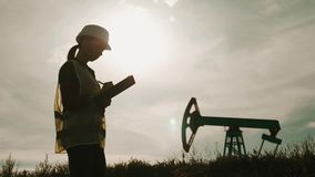 Silhouette female engineer writing on clipboard in oil field. Female wearing white helmet and work clothes. Industrial stock video footage