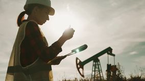 Silhouette female engineer writing on clipboard in oil field. Female wearing white helmet and work clothes. Industrial. Oil and gas concept stock footage