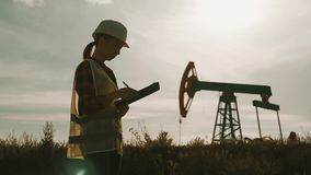 Silhouette female engineer writing on clipboard in oil field. Female wearing white helmet and work clothes. Industrial stock footage