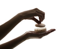 Silhouette of female hands holding face powder on white background stock image