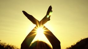 Silhouette of female hands at sunset in the shape of wings. The girl holds them crossed over her head and waves like a. Bird against the bright rays of the stock video footage