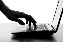 Silhouette of a female hands typing on the keyboard of the netbook Stock Photography