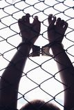 Hand holding fence. Silhouette of female holding fence background unfreedom concept Stock Images