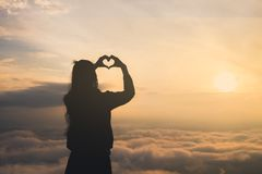 Silhouette of female holding hands in heart shape. Sunrise in the background. Summer vacation and travel concepts stock image