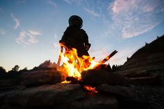 Silhouette female human holding wooden stick for a fire in the night by the forest Stock Photos