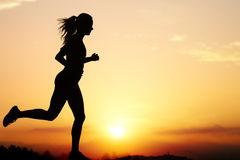 Silhouette of female jogger at sunset. Close up action Silhouette of female jogger at sunset.Girl backlit against intense orange sky Stock Photography