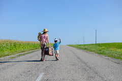 Silhouette of female with kids walking on the. Back view of female with children walking on the countryside rural road on sunny blue sky outdoors background Stock Images
