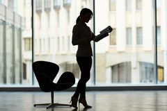Silhouette of Female Manager. Profile view of unrecognizable manager standing at spacious office with panoramic windows and studying document with concentration Royalty Free Stock Image