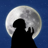 Silhouette of female muslim on blue moon Royalty Free Stock Photo