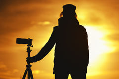 Silhouette of Female photographer against sunset Stock Image