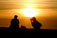 Silhouette of female photographer at sunset Royalty Free Stock Photos