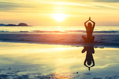Silhouette of female practicing morning yoga Stock Images