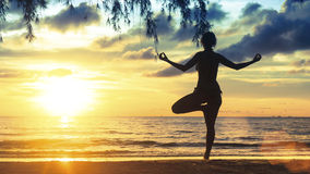 Silhouette  female practicing yoga on the beach at magnificent sunset. Royalty Free Stock Image