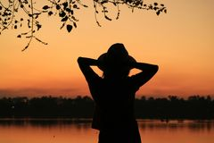 Silhouette of a female relaxing on the waterfront at dusk Stock Images