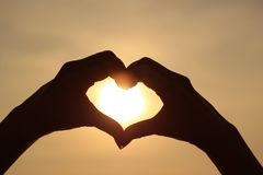 Silhouette of female`s hand posing LOVE HEART sign against the shiny rising sun. Nature Background stock images