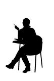 A silhouette of a female sitting on a school chair royalty free illustration