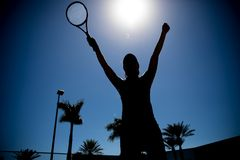 Silhouette of female tennis match winner. Silhouette of female tennis player standing with arms raised, celebrating victory against the sky Royalty Free Stock Images