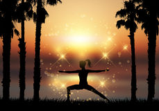 Silhouette of female in yoga pose in tropical landscape Stock Photos