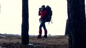 Silhouette femelle avec le sac à dos augmentant dans le mouvement lent de forêt banque de vidéos