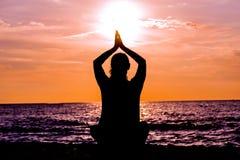 Silhouette femelle de lotos de yoga sur la belle plage pendant le coucher du soleil Photos libres de droits
