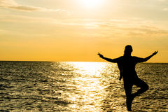 Silhouette femelle de vriksasana de yoga sur la belle plage pendant le coucher du soleil Photos stock