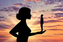 Silhouette feminist holding a small man. stock photography