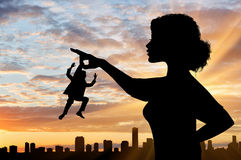 Silhouette feminist holds in his hand the little man against the backdrop of the cityscape. Concept of feminism royalty free stock photo