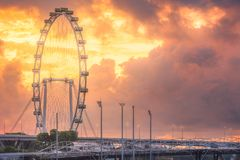 Silhouette of ferris wheel with cloud Singapore. Silhouette of ferris wheel with orange cloud on background during sunset, Singapore Stock Photos