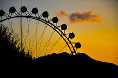 Silhouette of a ferris wheel at sunset Stock Photos