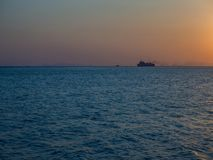 Silhouette of a ferry in the rays of the setting sun with clouds stock photo