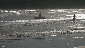 Silhouette of few people paddling out on boards at ocean waves at sunset. Tourists learning to surfing during summer. Trip. Beautiful seascape at background stock video footage