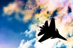 Silhouette of a fighter plane on a background of iridescent sky clouds and sun.  Royalty Free Stock Photos
