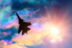 Silhouette of a fighter plane on a background of iridescent sky clouds and sun Royalty Free Stock Image