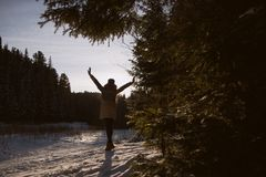 Silhouette of a girl in winter forest. Silhouette the figure of a girl in a parka, hat, fluffy mittens, standing with outstretched arms, facing the sun in the Royalty Free Stock Photo