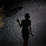 Silhouette of the figure of a young girl in the rain, happy young woman holding an umbrella that blows away royalty free stock photo