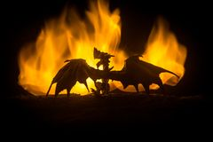 Silhouette of fire breathing dragon with big wings on a dark orange background royalty free stock photo
