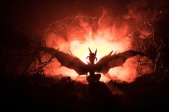 Silhouette of fire breathing dragon with big wings on a dark orange background. Horror image royalty free stock photography