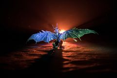 Silhouette of fire breathing dragon with big wings on a dark orange background. Horror image. Silhouette of fire breathing dragon with big wings on a dark orange royalty free stock photos