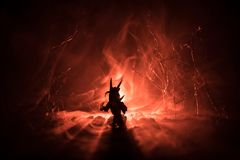 Silhouette of fire breathing dragon with big wings on a dark orange background. Horror image. Silhouette of fire breathing dragon with big wings on a dark orange royalty free stock image